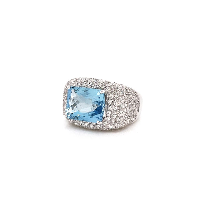 This gorgeous ring features a rectangular cushion cut aquamarine weighing 4.60 carats mounted in a four claw, open back setting. The vibrant gemstone is beautifully surrounded by a cluster of round brilliant cut diamonds totalling to an approximate