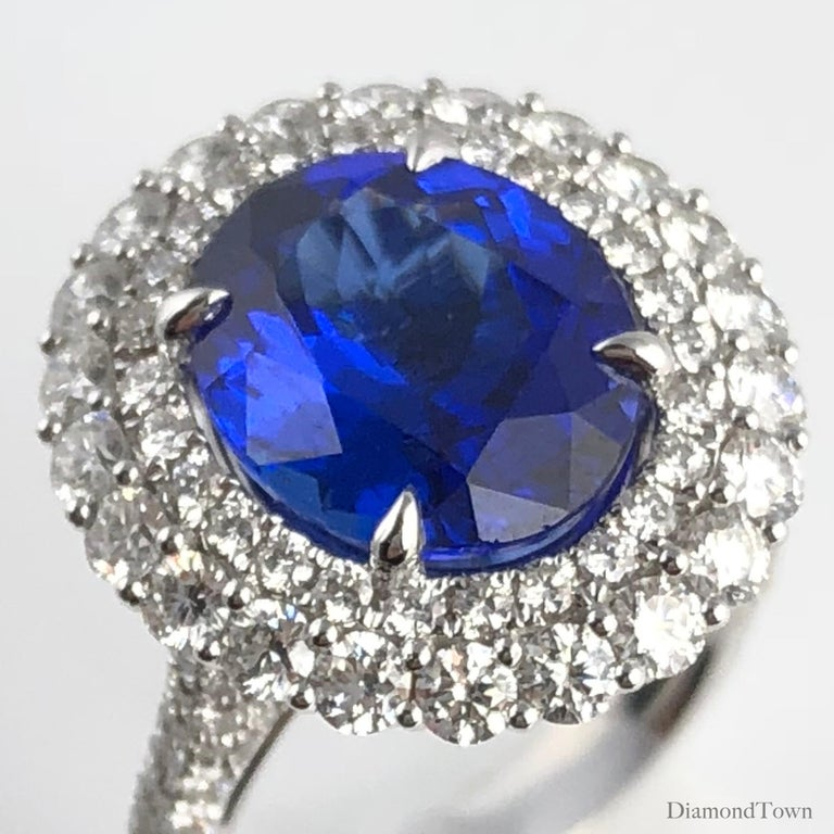 This gorgeous ring holds a 4.64 carat oval cut Tanzanite, surrounded by a double halo of round white diamonds. Additional diamonds placed along the side shank, as well as in the decorated under gallery bring the total diamond weight is 2.01