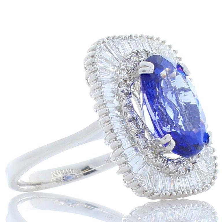 A 4.66 carat vivid bluish-violet tanzanite is perfectly saturated. Sourced near the footfills of Mt. Kilimanjaro in Tanzania, this oval gem measures 12.52 x 9.7mm and is vivid bluish-violet displaying flashes of red when rocked. Its clarity &