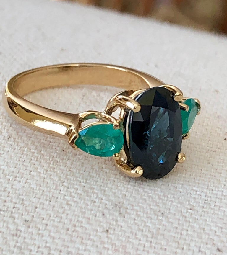 This Unique Natural Blue Sapphire and Colombian Emerald Engagement Cocktail Three Stone Ring is made of Rich Yellow Gold  18 Karat. Featuring  a  4.07 Carat Natural Sapphire Cobalt Blue, Oval Cut, VS. Sapphire Measurements: 11.50mm x 8.00  Accent