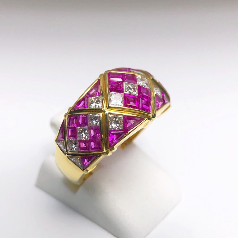 Designed with 4.78 carats of square calibre cut Pink Sapphires and 1.20 carats of princess cut White  Diamonds, this vintage ring remains timeless. Set in 18 karat yellow gold, the stone portion of the ring  measures approximately 7/8
