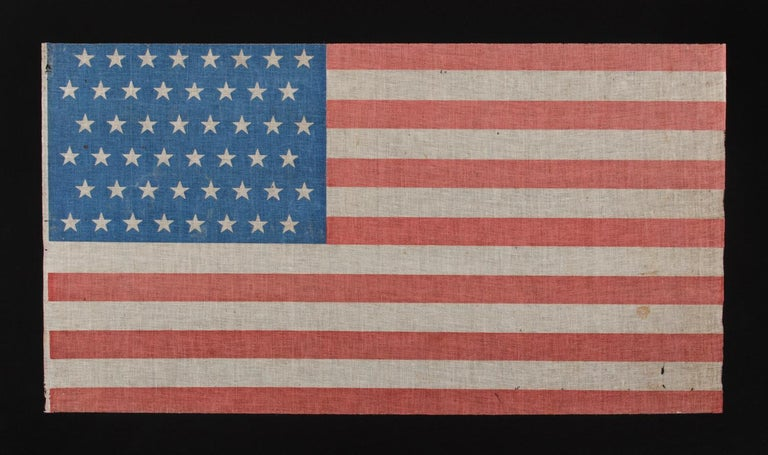 48 STARS IN STAGGERED ROWS ON A PARADE FLAG WITH A BRILLIANT, CORNFLOWER BLUE CANTON, 1896-1918  48 star American national parade flag, printed on coarse cotton, with an attractive, cornflower blue canton and scarlet red stripes.  On June 24th,