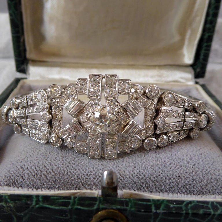 An Art Deco diamond bracelet comprised of panel links which  encompass old European cut, single cut, old Swiss Cut and trap cut diamonds.  The central panel tapering down to a single line of old round brilliant cut diamonds, grain set within square