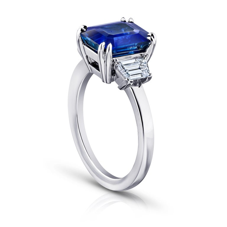 4.86 carat emerald cut blue sapphire with trapezoid diamonds .77 carats set in a platinum ring.
