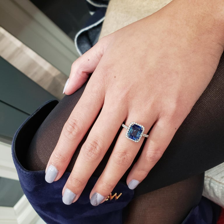 Creative and expertly hand-crafted; A dazzling halo set with round diamonds accent the 4.88 carat blue sapphire center stone. Finished with a pave of diamonds encircling the 18k white gold composition. Weight of the accent diamonds is 0.33 carats