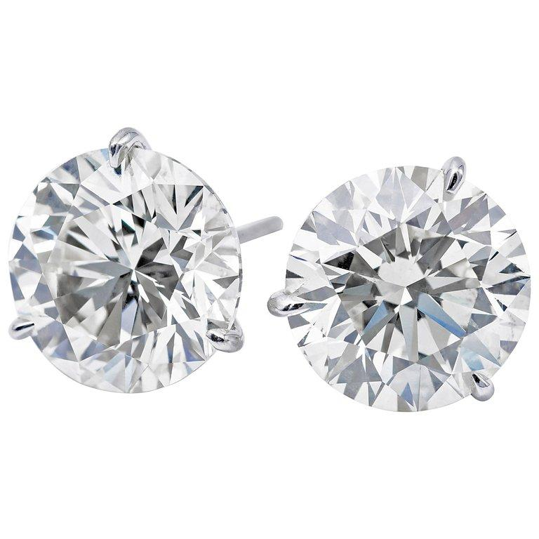Diamond stud earrings weighing 4.89 carats in a four prong 18k white gold champagne setting. Color H-I Clarity SI3-I1