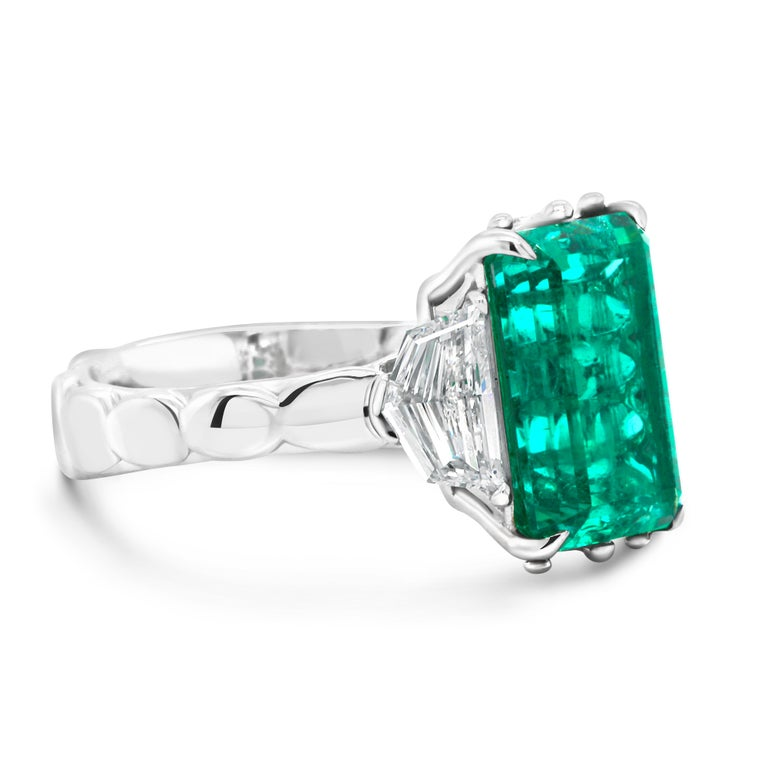 18 KT White Gold Ring featuring a no-oil certified exceptional 4.9ct Russian Emerald flanked by shield-shaped colorless Diamonds totaling 0.94 CTW (color F, clarity VS).  Rare Emerald used in this ring has gorgeous color and amazing clarity which