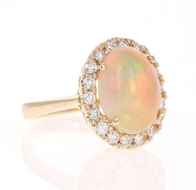 Simply beautiful Opal and Diamond 14 Karat Yellow Gold Ring.   This ring has a lovely Oval Cut Ethiopian-Origin Opal that weighs 4.35 Carats and has flashes of orange, green, red and yellow shining bright. There are 18 Round Cut Diamonds that weigh