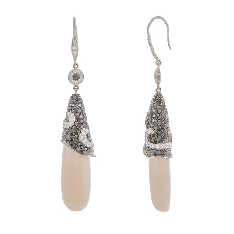Dramatic and rare, these beautiful pair of earrings features 49.53 carats white coral drops caped by 128 pieces of black diamonds weighing approximately 1.60 carats in total further suspended with diamond set surmount with a hook-back mechanism with