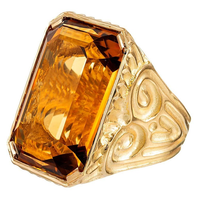 A unique scrolling design graces the sides of this generous ring, made of 18 karat yellow gold and handsomely appointed with a 49.64 carat emerald cut citrine. Suitable for a lady or gentleman, size 7 can be resized on request.