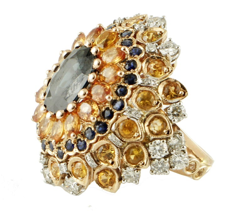 Beautiful cluster ring in 14k rose gold structure. The ring displays a big 4ct blue sapphire stone in the centre, surrounded by several crowns of multicolor sapphires, blue sapphires and white diamonds.  This ring is totally handmade by Italian