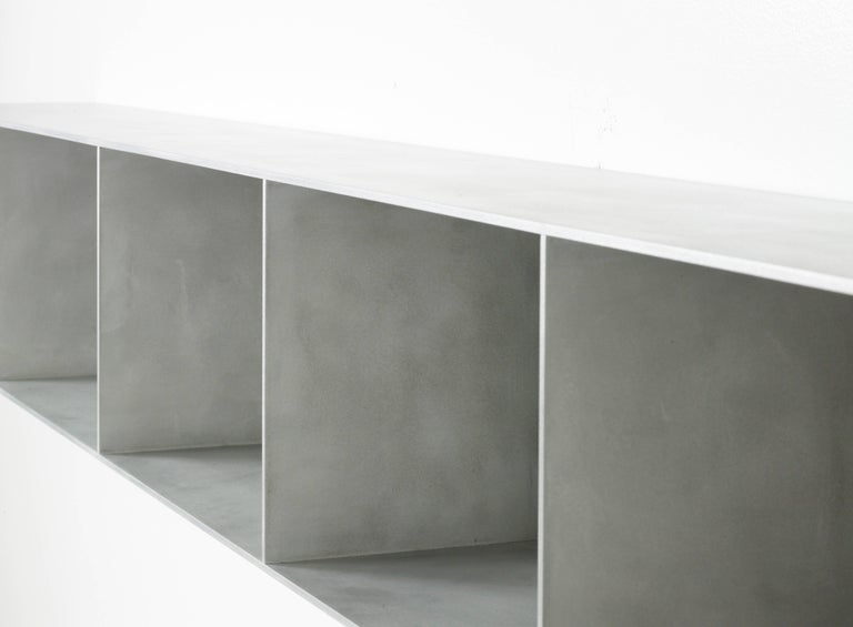 The Minimalist wall-mounted 4G shelf is sculpted out of 1/4 inch thick, wax-polished aluminum. Each shelf has an inset welded U-channel that spans the length of the shelf and easily mounts on included custom-bent steel Z-clips. Each bay of this