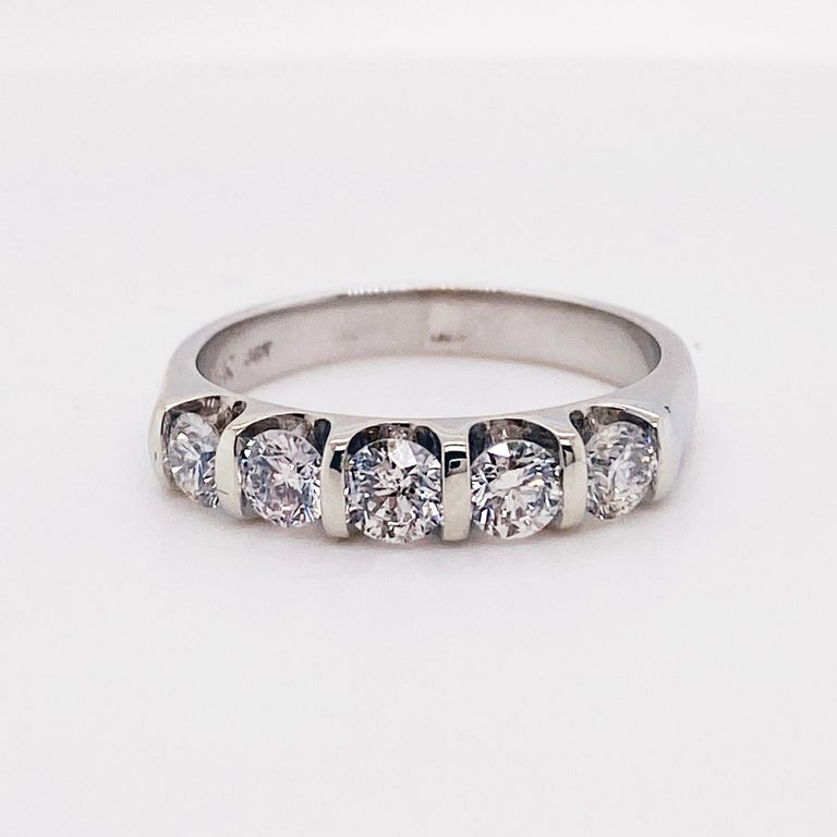 The five diamond band is a classic anniversary band have round brilliant diamonds. The round brilliant diamonds have a total weight of .75 carats and are set in vertical channel setting that are modern and clean! The ring is made with 14 karat white