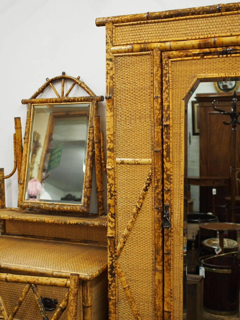 Rare five-piece bamboo and rattan bedroom suite. Comprising a wardrobe, dressing table, wash stand, and two bedroom chairs. The mirror door wardrobe has a central hanging space and rattan lined interior, above a base drawer and bamboo feet. The