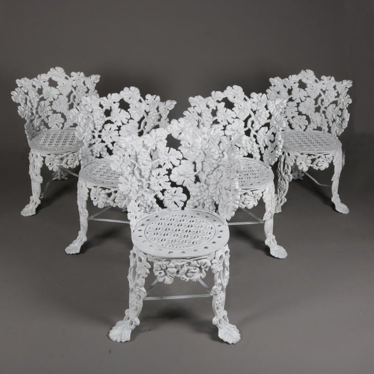 Set of 5 Victorian reticulated garden chairs features cast iron construction in grape and leaf pattern and seated on cabriole legs terminating in stylized paw feet and painted white, 20th century  Measures: 29