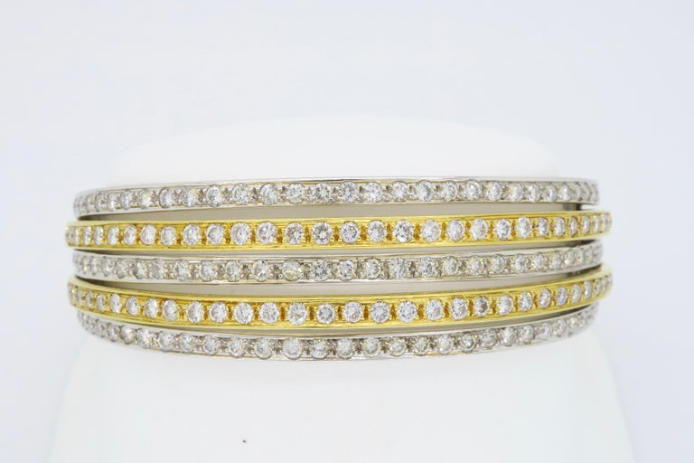 Unique 18k two tone gold diamond bangle featuring 5 elegant rows of Round Brilliant Cut Diamonds, totaling approximately 5.00CTW  Diamond Carat Weight: Approximately 5.00CTW Diamond Cut: 183 Round Brilliant Cut Diamonds Color: Average G-I Clarity: