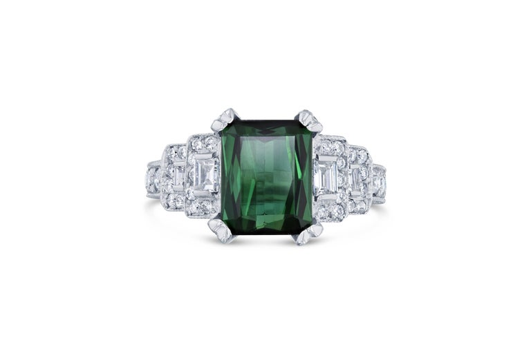 This ring has a mesmerizing Emerald cut Green Tourmaline weighing 3.71 Carats and 86 Round Cut Diamonds weighing 0.97 Carats as well as 4 Baguette Cut Diamonds weighing 0.33 Carats. The total carat weight of the ring is 5.01 Carats.   The Emerald