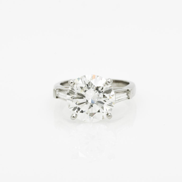 This platinum three-stone ring features a GIA certified 5.03 carat round brilliant cut diamond with J coloring and SI1 clarity. Flanking the center diamond are two tapered baguette diamonds with a combined approximate weight of 0.30 carats with G