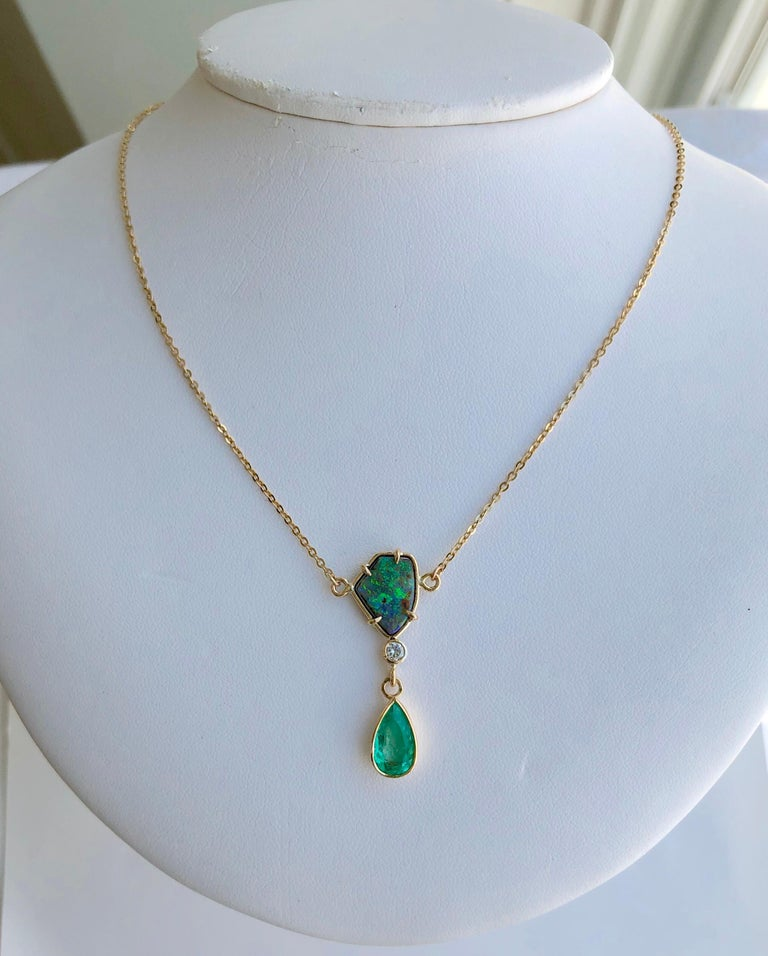 This stylish necklace featuring a gorgeous 1.50 carat natural Colombian emerald pear cut and a free form Australian boulder opal 3.50 carat with great play of colors. The pendant necklace also feature a round diamond approx 0.10cts. This beautiful