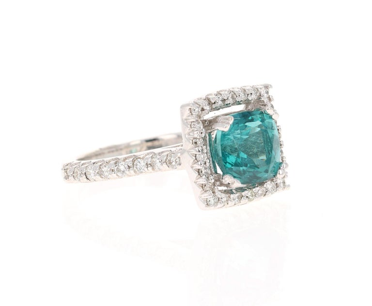 This ring has a 4.67 carat Apatite in the center of the ring and is surrounded by a halo of 34 Round Cut Diamonds that weigh 0.44 carat. The clarity of the diamonds are VS and the color is H. The total carat weight of the ring is 5.11 carats.    The
