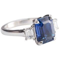 5.12 Carat Natural Emerald Cut Vivid Blue Sapphire and Diamond Three-Stone Ring