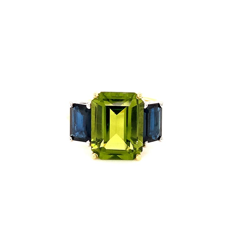A beautiful pairing of bright colors and sleek shapes form this modern version of a classic 3-stone ring. This stylish ring features a gorgeous, 5.12 carat emerald-cut peridot flanked on either side by emerald-cut rich blue sapphires. The peridot