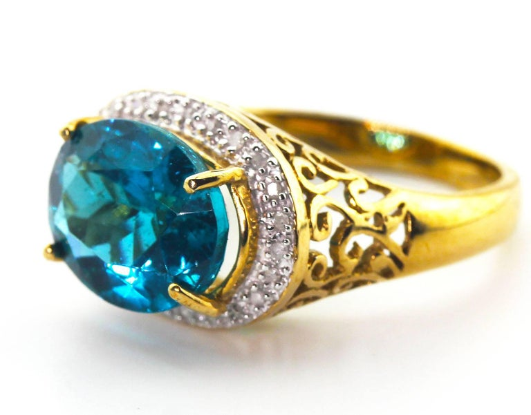 This flawless glittering 5.2 Carat unique natural blue Apatite from Madagascar is adorned with tiny little sparkling diamonds set in 10 KT yellow gold ring.  The Apatite is 12 mm x 10 mm and the ring is a size 7.5 sizable.