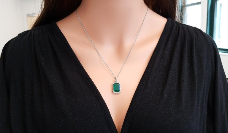 This is a 5.23 carat radiant cut emerald that takes the spotlight on this elegant dangle pendant in a prong setting with measurements of 13.5mm x 9.5mm. The gem origin is Zambia. The transparency and color is what you want. The luscious green of the