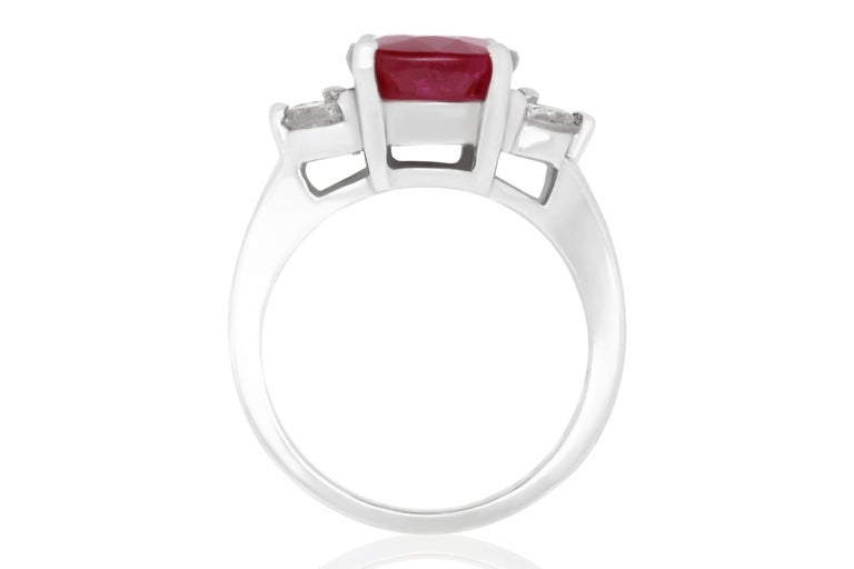 Material: 18k White Gold Gemstones: 1 Oval Ruby at 5.24 Carats. Measuring 9 x 7 mm. Diamonds: 4 Brilliant Round White Diamonds at 0.57 Carats. SI Clarity / H-I Color.  Ring Size: 6.5. Alberto offers complimentary sizing on all rings.  Fine one-of-a