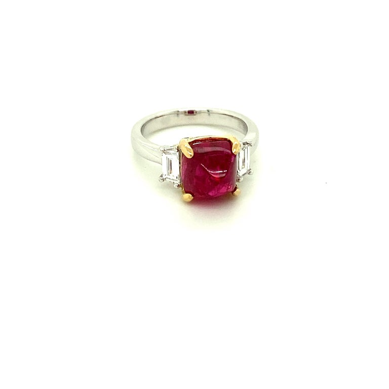 5.28 Carat Burmese Red Spinel Sugarloaf and White Diamond Gold Engagement Ring:  A beautiful ring, it features a stunning 5.28 carat unheated Burmese red spinel sugarloaf with baguette white diamonds on both sides of the spinel weighing 0.49 carat.