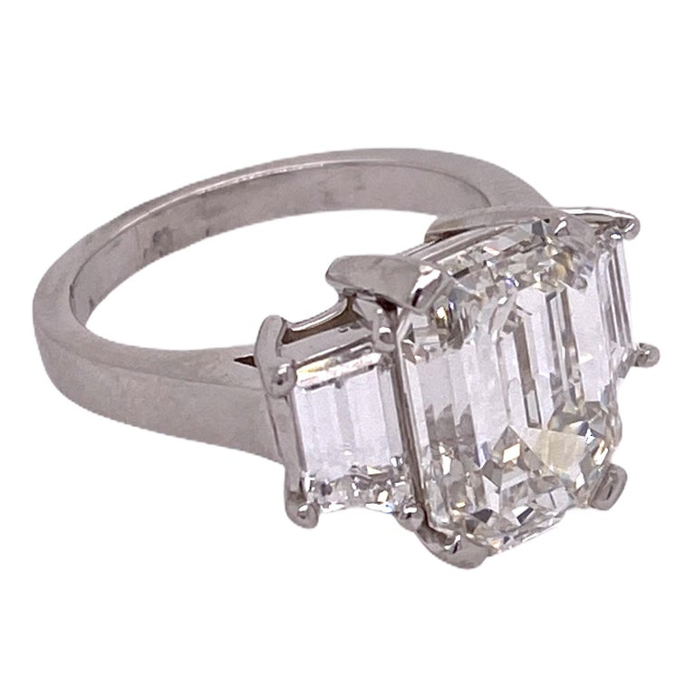 Stunning emerald cut diamond engagement ring handmade in platinum. The emerald cut diamondweighs 5.28 carats and is graded H color and VS2 clarity by the GIA. The two side trapazoid cut diamonds weigh 1.00 carat total weight. The platinum mounting
