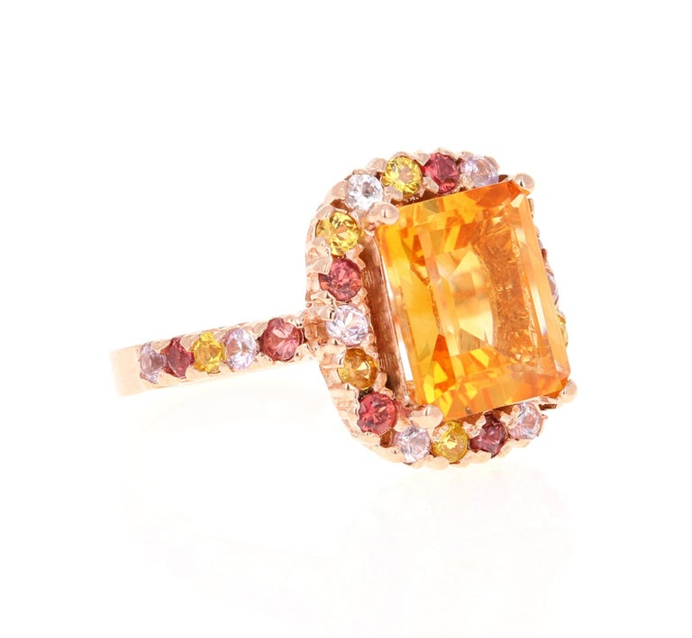 This gorgeous ring has a beautiful Emerald Cut Citrine Quartz weighing 3.79 Carats and is surrounded by a total of 28 Multi Sapphires weighing 1.50 Carats. Each stone is handpicked and carefully curated to create a unique piece by our in-house