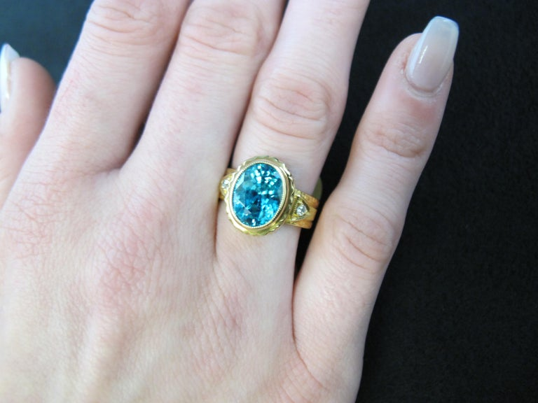 This stunning 5.34 carat blue zircon displays brilliant color and its beauty is well-matched by the exquisite  craftsmanship of this handmade ring. The 18k yellow gold bezel showcasing the center stone and the diamond studded band have both been