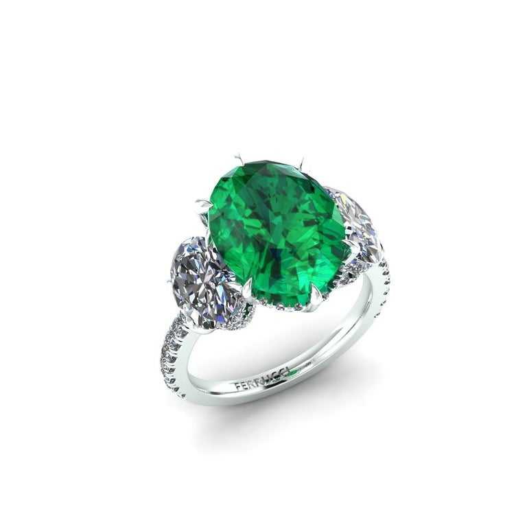 Eye Clean 5.37 carat Oval Emerald, rare beauty, sided by two 1 carat each, white Oval diamonds, G color, VS2 clarity GIA Certified, clarity ranging, no fluorescence, made in Platinum 950, embellished by Pave' set white round diamonds on every side