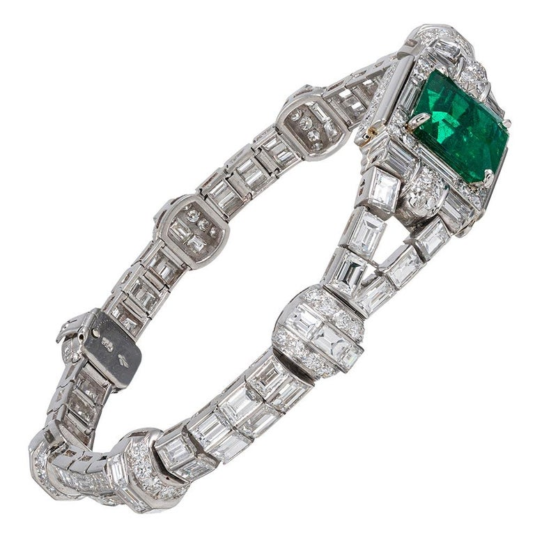 This important mid-20th century platinum bracelet has been artfully appointed with 12.50 carats of baguette and round brilliant cut white diamonds, however the most noteworthy component is the show-stopping emerald centerpiece. The gemstone weighs