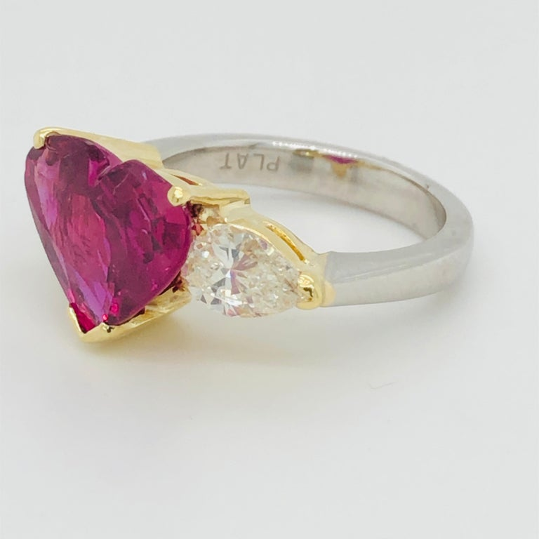 Offered here is a gorgeous heart shape ruby set in platinum and 18kt yellow gold ring with two pear shape diamonds.  Ruby: 5.43 carat Natural heart shape ruby, natural corundum, transparent purplish red  AGL cert# 1111899 measurements 10.67 x 13.53