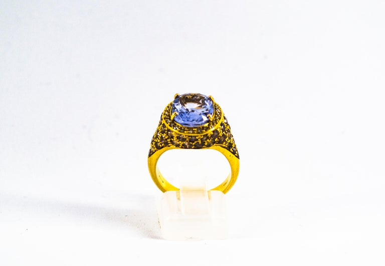 This Ring is made of 18K Yellow Gold. This Ring has 2.80 Carats of Brown Modern Round Cut Diamonds. This Ring has a 5.46 Carats Blue Oval Cut Sapphire. This Ring is available also with a central Emerald. Size ITA: 13 USA: 6.5 We're a workshop so