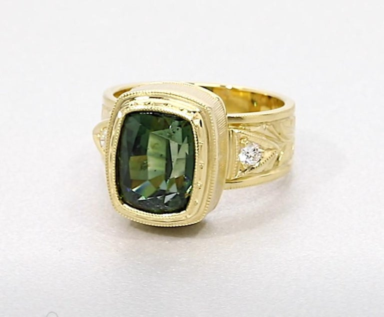 This gorgeous handmade 18k yellow gold ring features a 5.49 carat cushion-cut green tourmaline with color as lush as a tropical rainforest. Intricate engraving around the entire bezel is visible from every angle, and two round brilliant cut diamonds