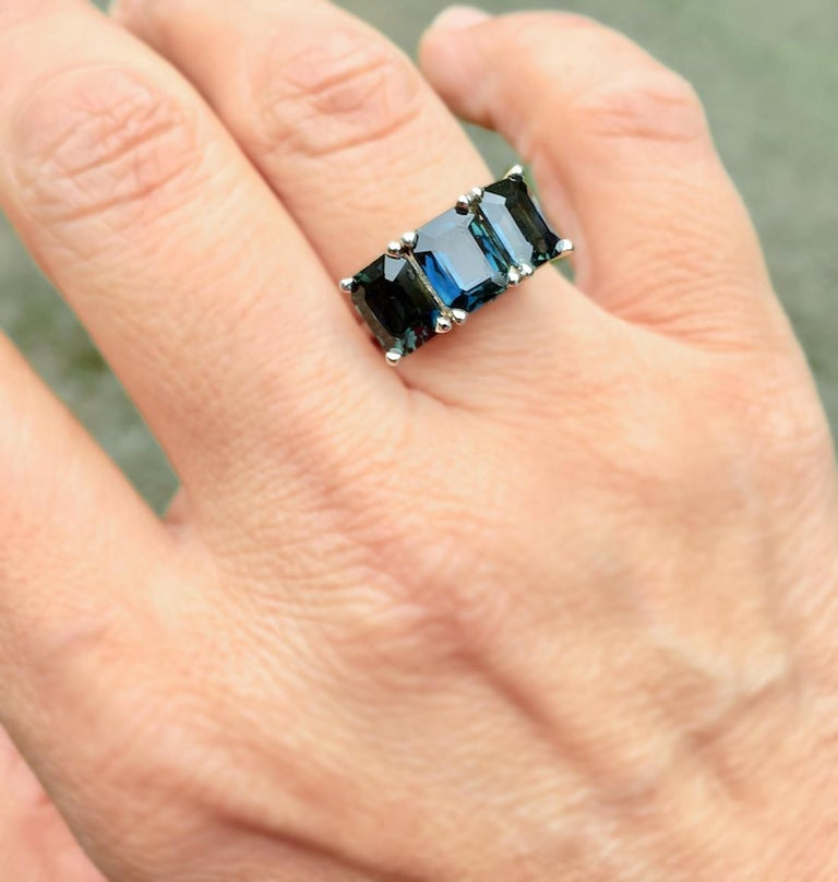A three perfectly matched contemporary stylish Natural Sapphire three-stone wedding engagement ring unheated emerald-cut Sapphire, displaying a most unique dark teal, greenish blue color. All 3 Sapphires emerald cut with an approximate combined