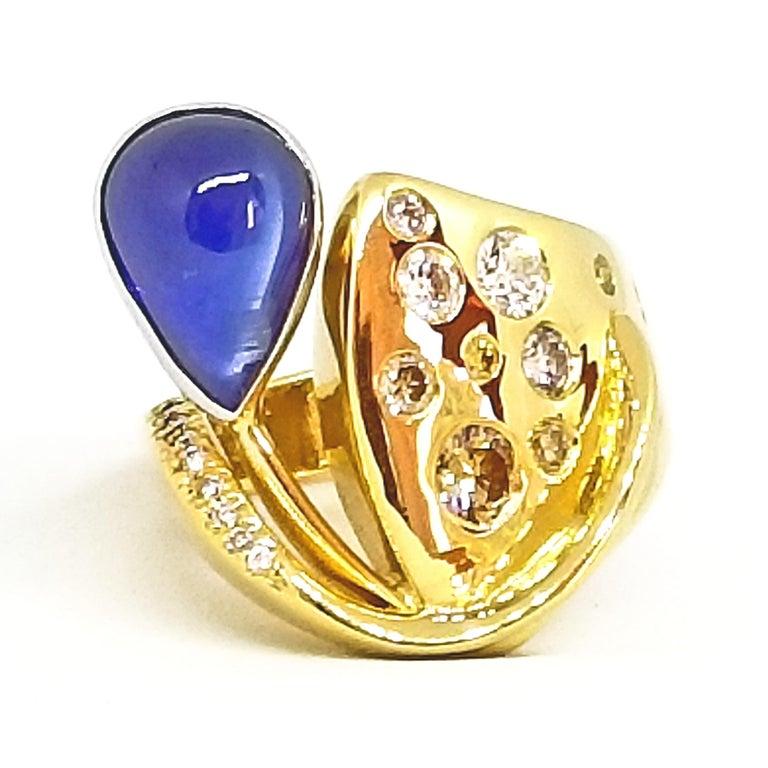 This one of a kind, artist designed and crafted Statement Ring features a 5.51 carat Sugarloaf Sapphire. The Tear Drop Shaped stone is a Translucent Medium Blue and is Bezel set in 18K White Gold. The Contemporary Asymmetric ring is Highly Polished