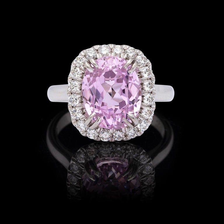 Think pink!! This Princess Diana design platinum ring features a pleasing oval-cut kunzite weighing 5.53 carats, set within a halo of 20 round brilliant-cut diamonds totaling 0.60 carat. The ring weighs 9.5 grams and is currently size 5.75, with