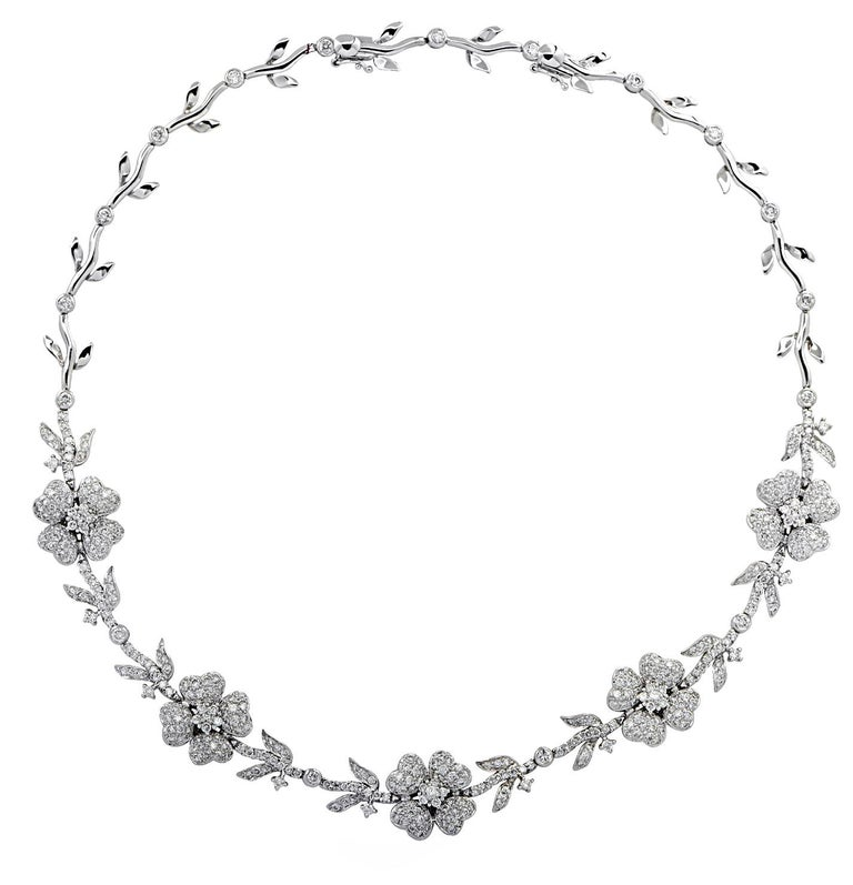 Enchanting necklace crafted in 18 karat white gold, featuring 280 round brilliant cut diamonds weighing approximately 5.75 carats total, G-H color, VS-SI clarity. A delightful diamond encrusted flower garland dances around the neck, capturing the