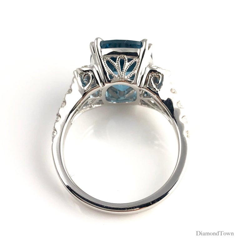 This gorgeous ring features a 5.79 carat cushion cut London Blue Topaz center, flanked by marquise cut diamonds on each side, as well as graduated round diamonds extending down the side shank. Intricate milgrain work makes this ring shine from all