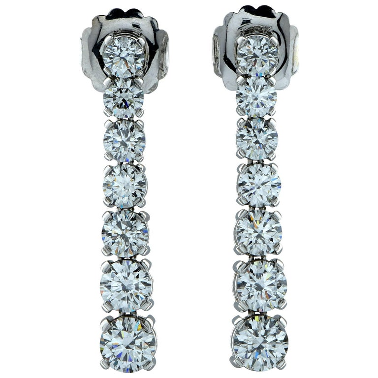 Stunning diamond drop earrings fashioned in platinum. Each of the 14 diamonds have been GIA certified and equal 5.91 carat total weight.  The diamonds are all graded D-F color and VS2-SI2 clarity. The dangle earrings measure 1.5 inches in length.