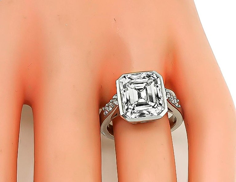 This stunning platinum engagement ring is centered with a sparkling emerald cut diamond that weighs 5.94ct. graded K-L color with VS2 clarity. The top of the ring measures 13mm by 11mm. It is stamped PLAT and weighs 11.2 grams. The ring is currently