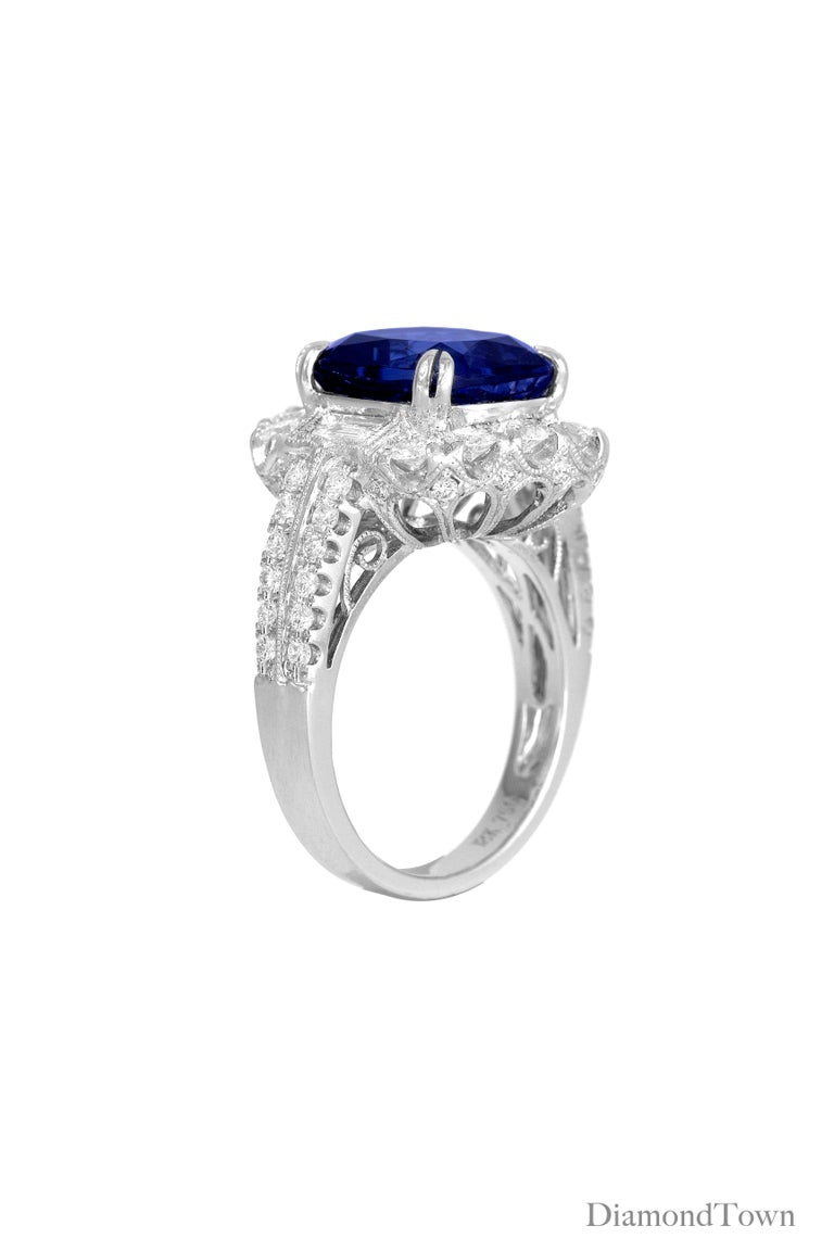 This ring sparkles with a 5.96 Carat Tanzanite center, flanked by 2 tapered baguette diamonds and a halo of round diamonds, and additional diamonds trailing down the side shank, bringing the total diamond weight to 1.47 carats. Milgrain work and a