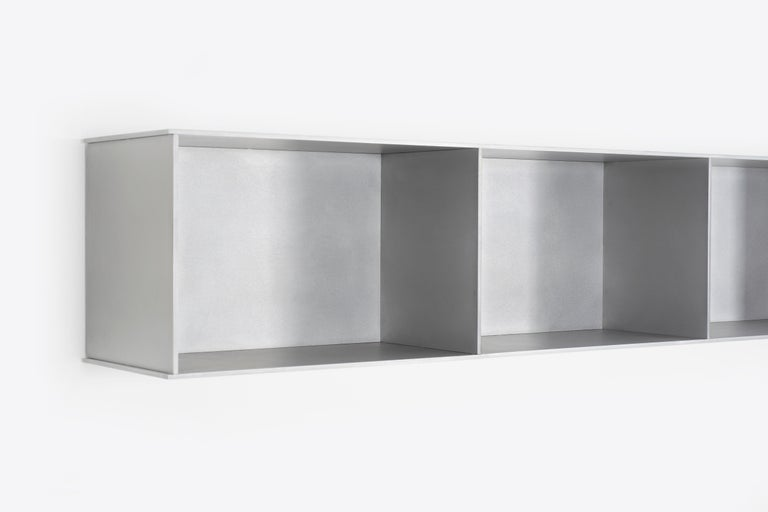 The Minimalist wall-mounted, 91 wide, 5G shelf is sculpted out of 1/4 inch thick, wax-polished aluminum. Each shelf has an inset welded U-channel that spans the length of the shelf and easily mounts on included custom-bent steel Z-clips. Each bay of