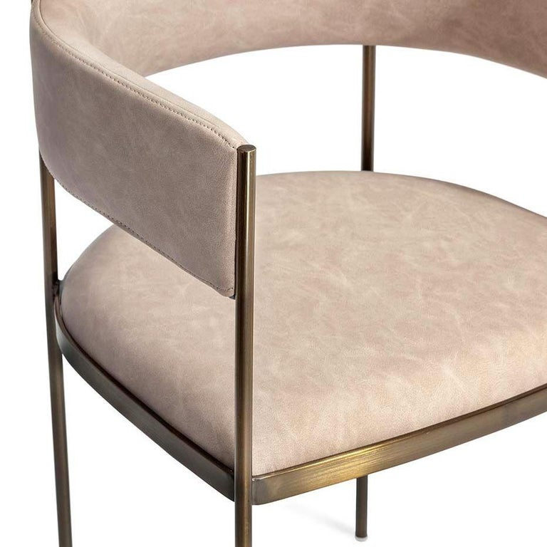 A sleek and elegant dining chairs with curved seat and backrest supported by a light steel structure.