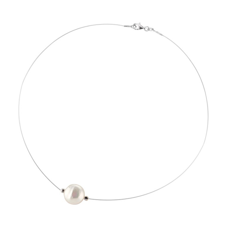 12.75mm butter style freshwater pearl and diamond necklace on an 18k white gold wire. Flat freshwater pearl with 2 round brilliant cut side diamonds. 16 inches.  1 flat white freshwater pearl, 12.75mm x 6.1mm  2 round brilliant cut diamonds, G-H SI
