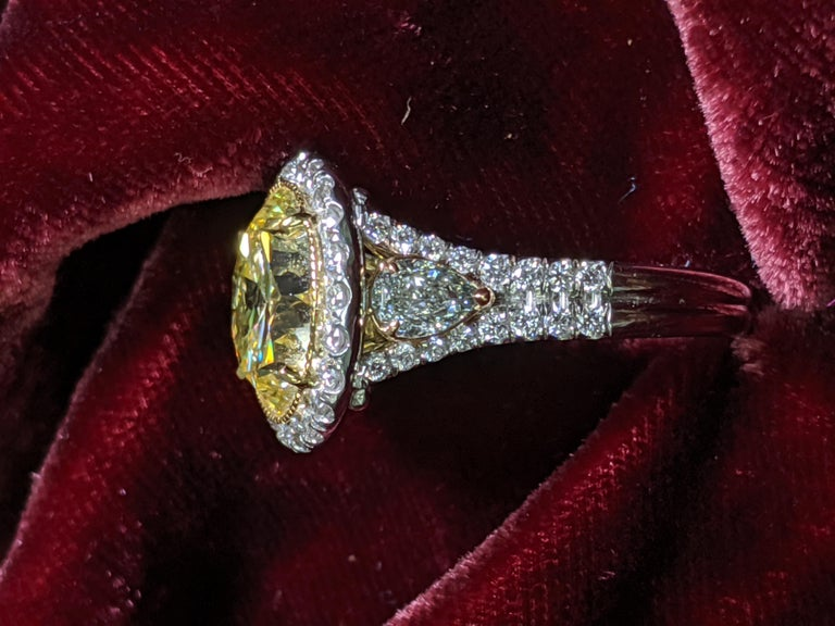 Rare SIX carat Fancy Intense Yellow Round Diamond mounted in a handmade Platinum mounting with side pear shape diamonds and smaller white diamond outline.  The ROUND shape is extremely rare in natural fancy color diamonds and definitely make a